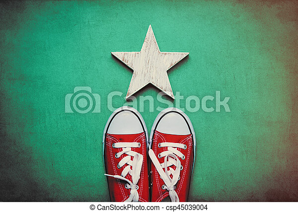 big red gumshoes and cute star shaped toy lying on the wonderful blue background - csp45039004