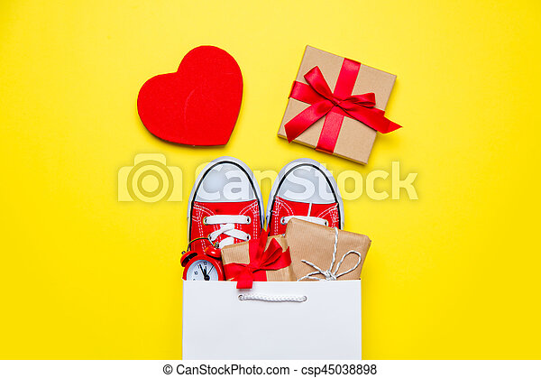 big red gumshoes, beautiful gifts and alarm clock in cool shopping bag and heart shaped toy on the wonderful yellow background - csp45038898