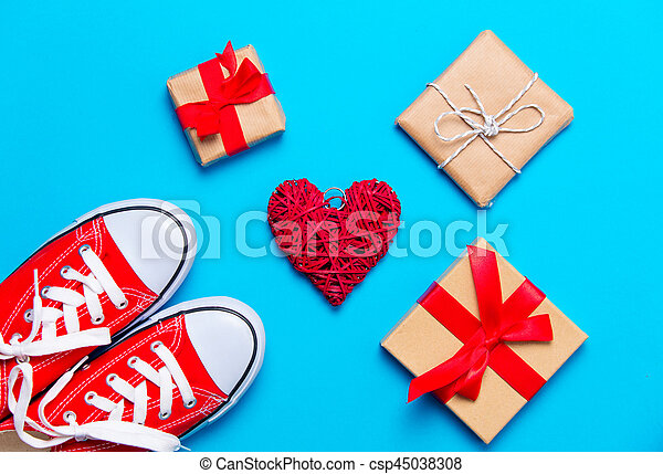 big red gumshoes, heart shaped toy and beautiful gifts on the wonderful blue background - csp45038308