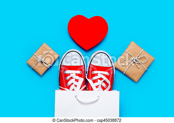 big red gumshoes in cool shopping bag, heart shaped toy and beautiful gifts on the wonderful blue background - csp45038872