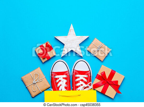 big red gumshoes in cool shopping bag, star shaped toy and beautiful gifts on the wonderful blue background - csp45038355