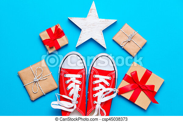 big red gumshoes, star shaped toy and beautiful gifts on the wonderful blue background - csp45038373