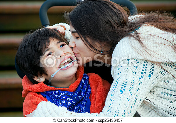 Big sister kissing disabled little brother seated in wheelchair - csp25436457