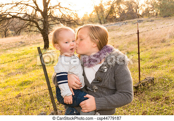 Big Sister Kissing Little Brother - csp44779187