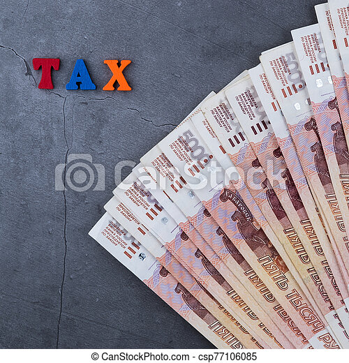 Big stack of Russian money banknotes of five thousand rubles lying on a grey cement background. - csp77106085