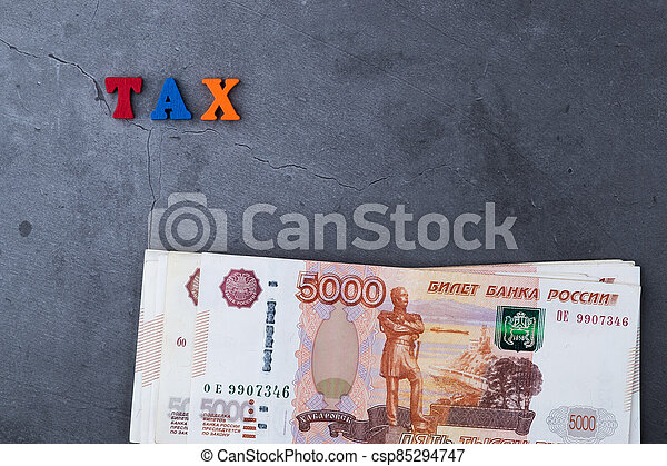 Big stack of Russian money banknotes of five thousand rubles lying on a grey cement background. - csp85294747