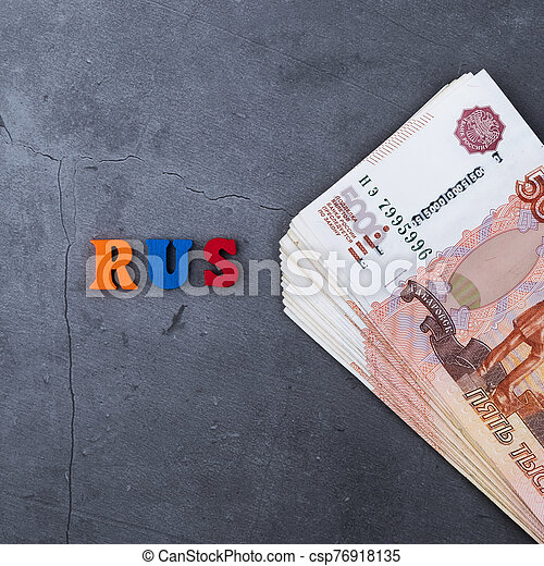 Big stack of Russian money banknotes of five thousand rubles lying on a grey cement background. - csp76918135