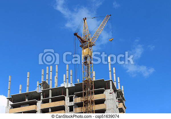 Big yellow stationary hoist on construction site part of picture