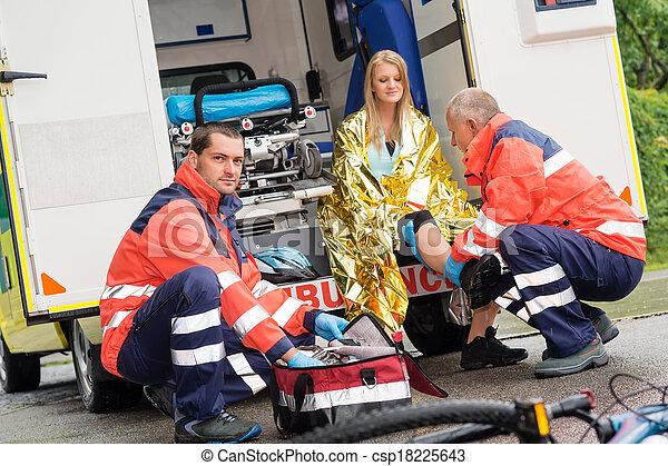 Bike accident woman emergency doctor checking leg - csp18225643