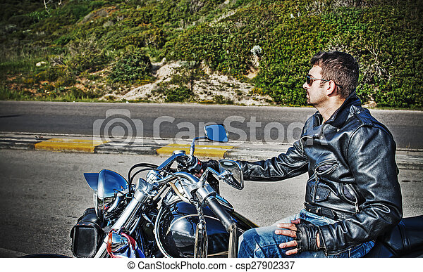 biker and classic motorcycle side view - csp27902337