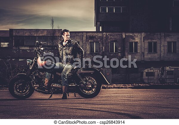 Biker and his bobber style motorcycle on a city streets  - csp26843914