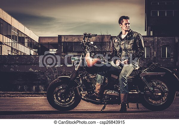 Biker and his bobber style motorcycle on a city streets  - csp26843915