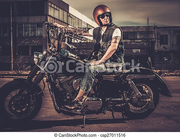 Biker and his bobber style motorcycle on a city streets  - csp27011516