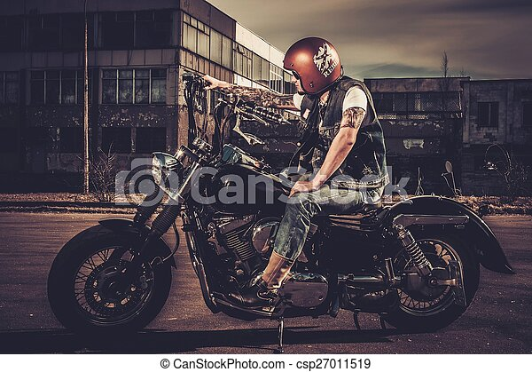 Biker and his bobber style motorcycle on a city streets  - csp27011519