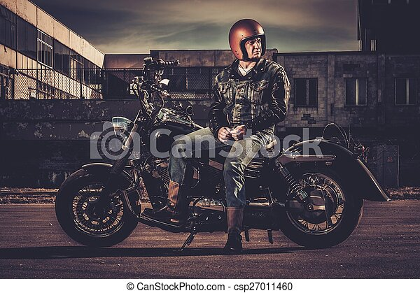 Biker and his bobber style motorcycle on a city streets  - csp27011460