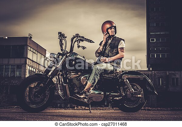 Biker and his bobber style motorcycle on a city streets  - csp27011468