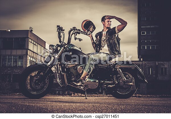 Biker and his bobber style motorcycle on a city streets  - csp27011451