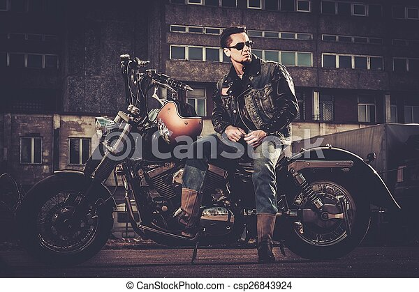 Biker and his bobber style motorcycle on a city streets  - csp26843924