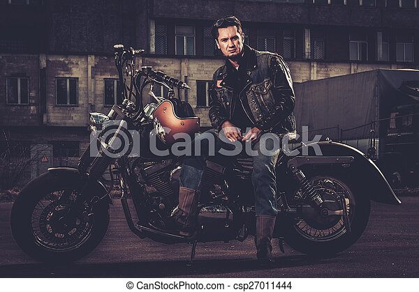 Biker and his bobber style motorcycle on a city streets  - csp27011444