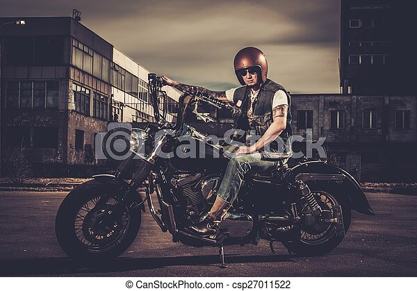 Biker and his bobber style motorcycle on a city streets  - csp27011522