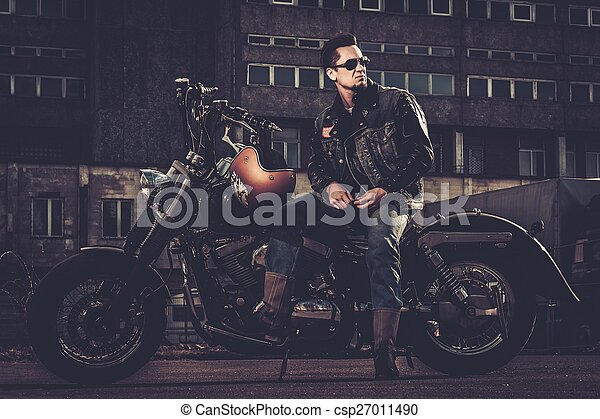 Biker and his bobber style motorcycle on a city streets  - csp27011490