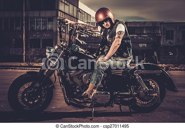 Biker and his bobber style motorcycle on a city streets  - csp27011495