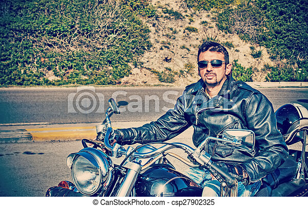 biker and his motorcycle in retro tone - csp27902325