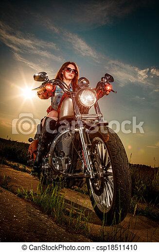 Biker girl sitting on motorcycle - csp18511410