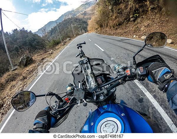 Biker Going up the a road in arunachal - csp87498167