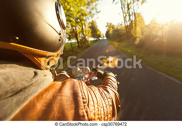 Biker riding motorcycle  in sunny morning - csp30769472