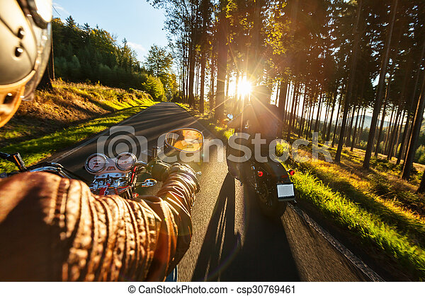 Biker riding motorcycle  in sunny morning - csp30769461