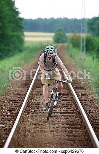 Biker riding on railway track - csp6429676