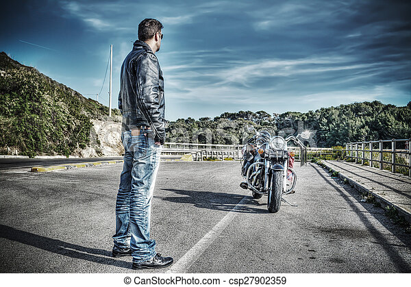 biker standing next to a classic motorcycle - csp27902359