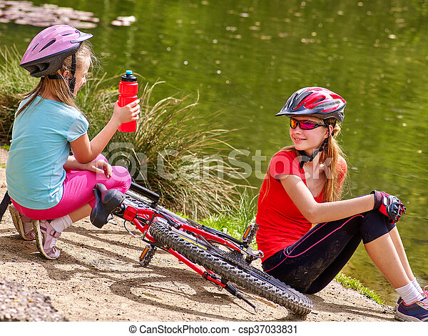 Bikes cycling family. Happy mother and daughter rides bicycle. - csp37033831
