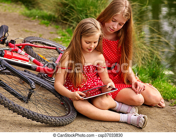 Bikes cycling girl into park. Children watch tablet pc. - csp37033830