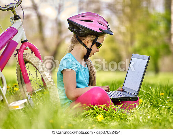 Bikes cycling girl wearing helmet in cycling sitting near bicycle and watch pc tablet. - csp37032434