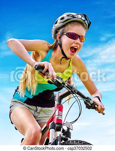 Bikes cycling girl wearing helmet rides bicycle aganist blue sky. - csp37032502