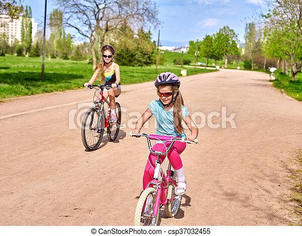 Bikes cycling girl wearing helmet riding on bicycle lane. - csp37032455
