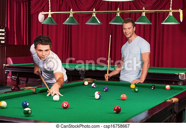 Poolspiel. Selbstbewusster junger Mann, der den Billardball mit einem Queue zielt, während sein Gegner Billiard Cue hält und im Hintergrund lächelt - csp16758667