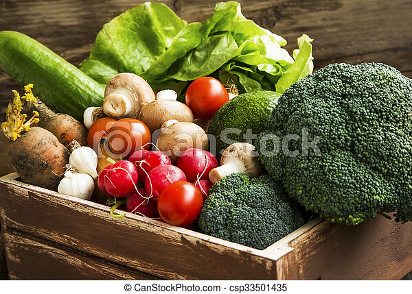 Bio vegetables in wooden crate with radish, salad, mushrooms, broccoli, tomatoes - csp33501435