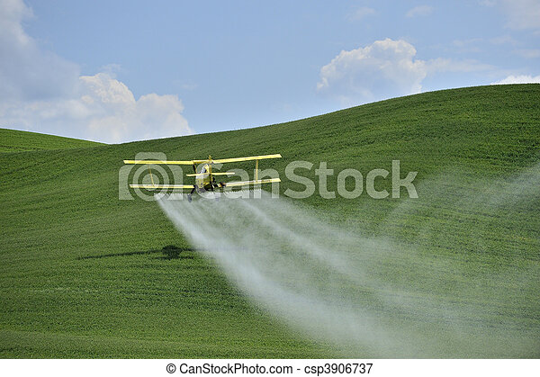 Biplane Crop Duster spraying a farm field. - csp3906737