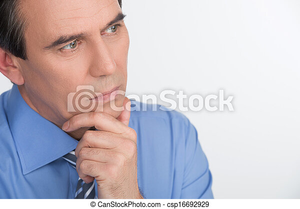 Birth of new business idea. Handsome mature businessman holding his hand on chin and thinking about something while standing isolated on white - csp16692929