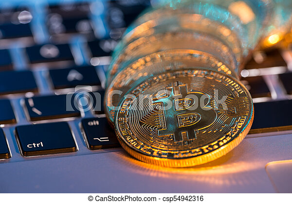 Bitcoin gold coins with laptop keyboard. Virtual cryptocurrency concept. - csp54942316