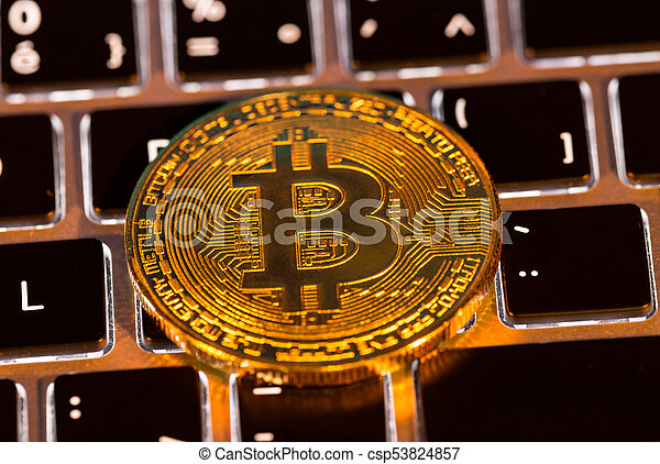 Bitcoin gold coins with laptop keyboard. Virtual cryptocurrency concept. - csp53824857