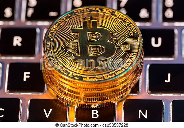 Bitcoin gold coins with laptop keyboard. Virtual cryptocurrency concept. - csp53537228