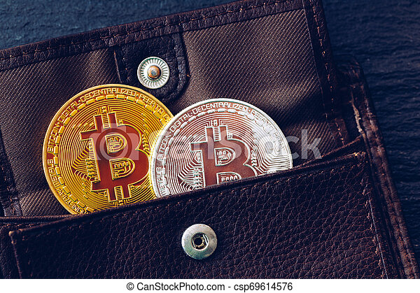 Bitcoin in brown leather wallet. Bitcoin, modern virtual cryptocurrency. Profit from mining crypto currencies. Bitcoin gold coins with wallet, close-up. Virtual cryptocurrency concept. - csp69614576