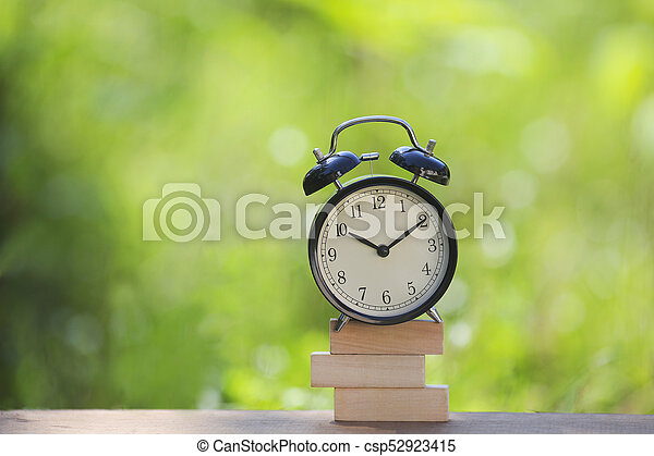Black alarm clock stacked on wooden bar with shallow DOF green background. Business / Time Management concept. - csp52923415