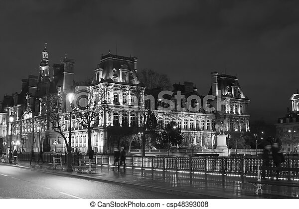 Black And White Image Of People Walk In Blurry Motion On Bridge Near Hotel De Ville At Night Paris Winter Time