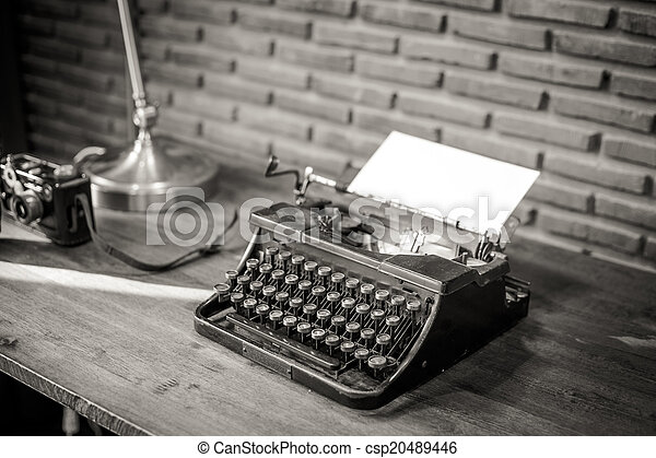 Black and white of an old typewriter with paper on a wooden tabl - csp20489446