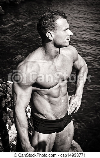 Black and white photo of attractive muscular young man by the sea - csp14933771